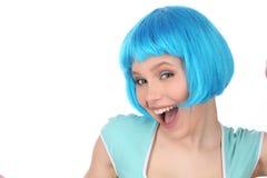 穿蓝色假发和衬衣的微笑的夫人 关闭 奶油被装载的饼干 免版税库存图片