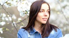 穿蓝色时髦的牛仔裤夹克的年轻可爱的亭亭玉立的妇女摆在开花的木兰树和花 股票录像