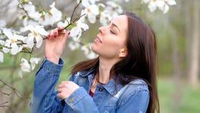 穿蓝色时髦的牛仔裤夹克的年轻可爱的亭亭玉立的妇女摆在开花的木兰树和花 影视素材