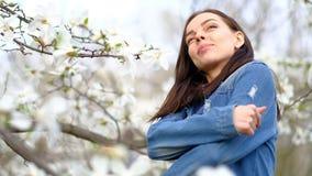 穿蓝色时髦的牛仔裤夹克的年轻可爱的亭亭玉立的妇女摆在开花的木兰树和花 股票视频
