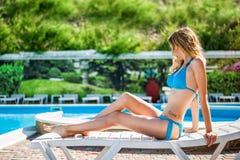 穿蓝色比基尼泳装的妇女在海滩躺椅放松 免版税库存照片