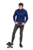 穿蓝色田径服夹克和紧的牛仔裤的微笑的确信的行家站立在滑板 免版税库存图片