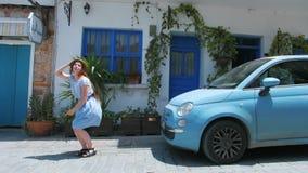穿蓝色礼服和跳跃在减速火箭的汽车前面的街道上的美丽的活跃红头发人年轻女人 影视素材