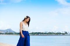 穿蓝色裤子的青少年的女孩走在海滩在威基基 免版税库存照片