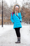 穿蓝色戴头巾外套的全长年轻可爱的白肤金发的妇女漫步在多雪的冬天城市公园 自然冷的季节生气勃勃 图库摄影