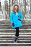 穿蓝色戴头巾外套的全长年轻可爱的白肤金发的妇女漫步在多雪的冬天城市公园 自然冷的季节生气勃勃 免版税库存图片