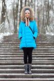 穿蓝色戴头巾外套的全长年轻可爱的白肤金发的妇女漫步在多雪的冬天城市公园 自然冷的季节生气勃勃 库存照片