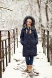 穿蓝色戴头巾外套的年轻可爱的妇女享受漫步在冬天森林里户外 自然冷的季节生气勃勃概念 库存图片