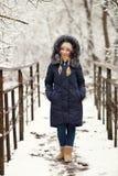 穿蓝色戴头巾外套的年轻可爱的妇女享受漫步在冬天森林里户外 自然冷的季节生气勃勃概念 免版税库存照片