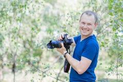 穿蓝色T恤杉的可爱的男性摄影师画象户外在夏日 有一台DSLR照相机的年轻人在手上 免版税库存图片