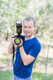 穿蓝色T恤杉的可爱的男性摄影师画象户外在夏日 有一台DSLR照相机的年轻人在手上 免版税库存照片