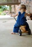 穿蓝衣的男孩少许滑行车 免版税库存图片