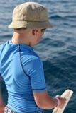 穿蓝衣的男孩捕鱼衬衣船 免版税库存照片