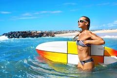 穿蓝衣的男孩服务台女孩查找海运坐的冲浪 愉快的健康冲浪者妇女在海 旅行假期 免版税图库摄影