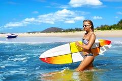穿蓝衣的男孩服务台女孩查找海运坐的冲浪 愉快的健康冲浪者妇女在海 旅行假期 免版税库存图片