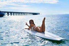 穿蓝衣的男孩服务台女孩查找海运坐的冲浪 愉快的健康妇女在海 旅行假期 Lifest 免版税库存图片