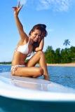 穿蓝衣的男孩服务台女孩查找海运坐的冲浪 愉快的健康妇女在海 旅行假期 Lifest 图库摄影