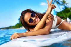穿蓝衣的男孩服务台女孩查找海运坐的冲浪 愉快的健康妇女在海 旅行假期 Lifest 库存照片