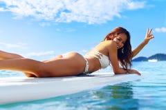 穿蓝衣的男孩服务台女孩查找海运坐的冲浪 愉快的健康妇女在海 旅行假期 Lifest 免版税图库摄影