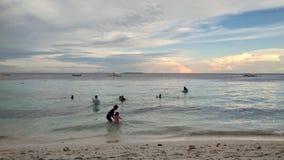 穿蓝衣的男孩服务台女孩查找海运坐的冲浪 免版税图库摄影