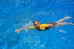穿蓝衣的男孩游泳水 免版税库存图片