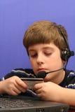 穿蓝衣的男孩看板卡使用年轻人的计&# 图库摄影