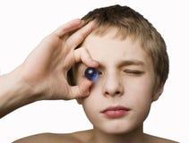 穿蓝衣的男孩眼睛藏品大理石 免版税库存图片