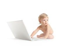 穿蓝衣的男孩被注视的膝上型计算机&# 免版税库存图片