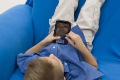 穿蓝衣的男孩palmtop 免版税图库摄影