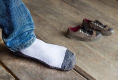 穿袜子的人在一木foor投入了一只脚 库存图片