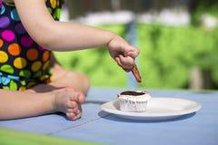 穿被察觉的泳装的逗人喜爱的婴孩品尝杯形蛋糕 免版税图库摄影