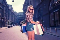 穿被摆正的衬衣和牛仔布连衫裤的时髦的妇女拿着购物袋 免版税库存图片