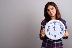 穿被检查的衬衣的年轻美丽的印地安妇女反对灰色 免版税库存图片