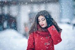 穿被编织的妇女发网和红色外套的年轻美丽的深色的妇女冬天画象盖在雪 降雪的冬天秀丽fashio 免版税库存照片