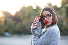 穿被编织的毛线衣的一个相当被晒黑的女孩的街道画象摆在街道上 复制空间 库存图片