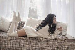 穿被编织的毛线衣的美丽的年轻深色的妇女休息o 库存照片