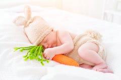 穿被编织的兔宝宝服装的逗人喜爱的两个星期年纪新出生的男婴 免版税库存图片