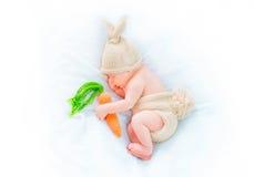 穿被编织的兔宝宝服装的逗人喜爱的新出生的男婴 库存图片
