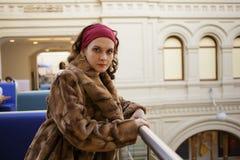 穿豪华冬天皮大衣的俏丽的女孩在商店中心 库存图片