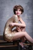 穿豪华金礼服的女孩模型坐木立场 免版税库存图片