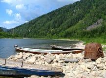 穿过一条河的小船在一个混杂的森林里 免版税库存图片
