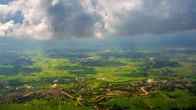 穿过云彩的光束在有绿草领域和山脉的Chiangrai市 地区射击被采取了thr 免版税库存照片