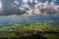 穿过云彩的光束在有绿草领域和山脉的Chiangrai市 地区射击被采取了thr 库存图片