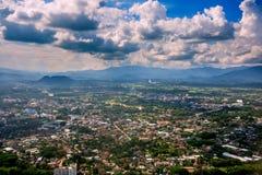 穿过云彩的光束在有绿草领域和山脉的Chiangrai市 地区射击被采取了thr 图库摄影