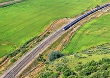穿过国家风景的现代火车 图库摄影