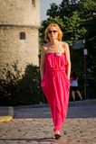穿过城市街道的红色礼服的女孩 免版税库存图片