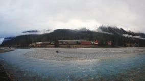 穿过山的长的货物火车在小河后用天蓝色的水在雨天期间 免版税库存照片