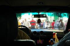 穿过拥挤的街的出租汽车司机 库存照片