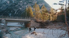 穿过有背包和吉他的两年轻女人岩石河在山的一座桥梁下 股票录像