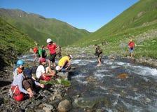 穿过河的小组登山人 免版税库存照片